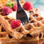 fork stuck in a stack of waffles topped with butter and raspberries