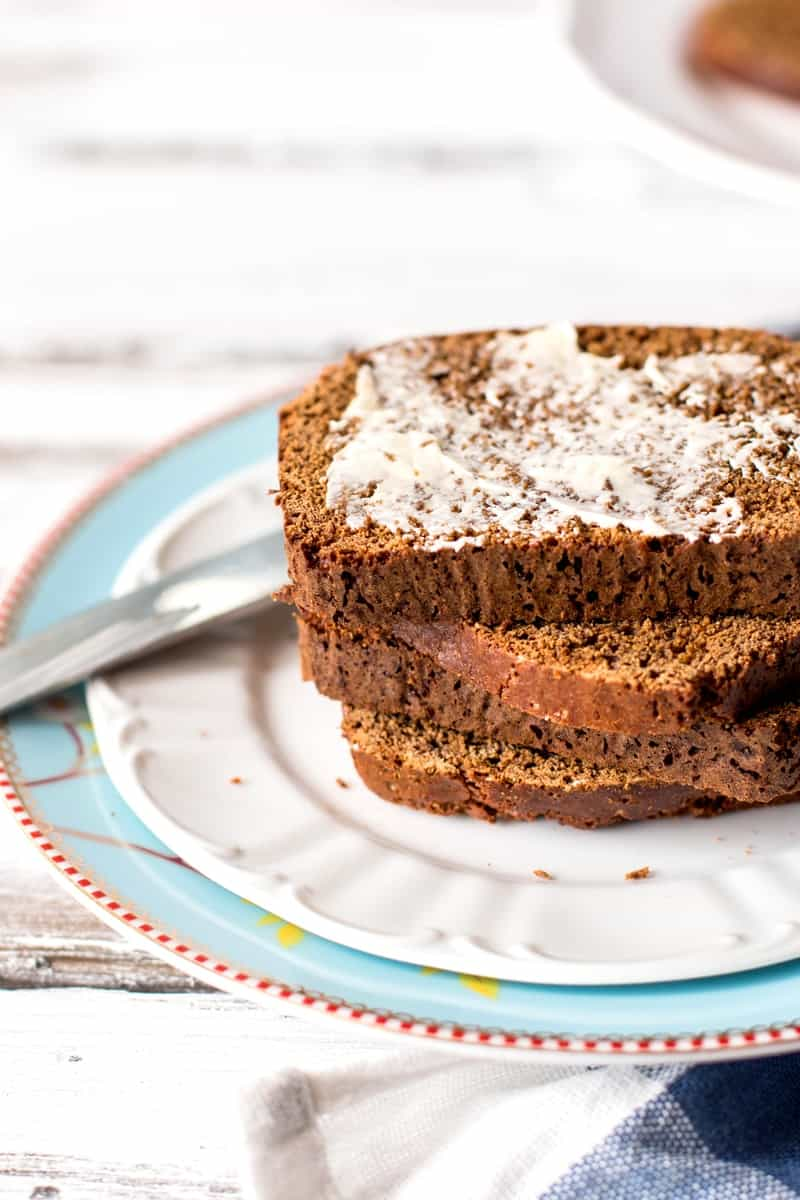 stack of sliced Dutch honey bread on a plate, top slice spread with butter