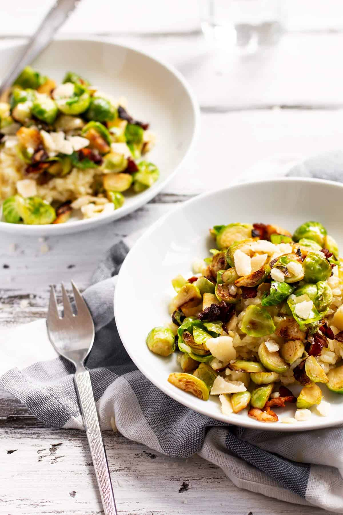 two plates filled with risotto with bacon and brussels sprouts