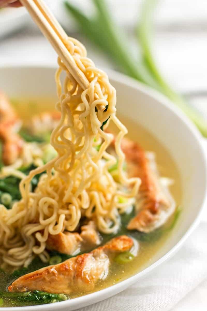 chopsticks holding Ramen noodles over a bowl of soup