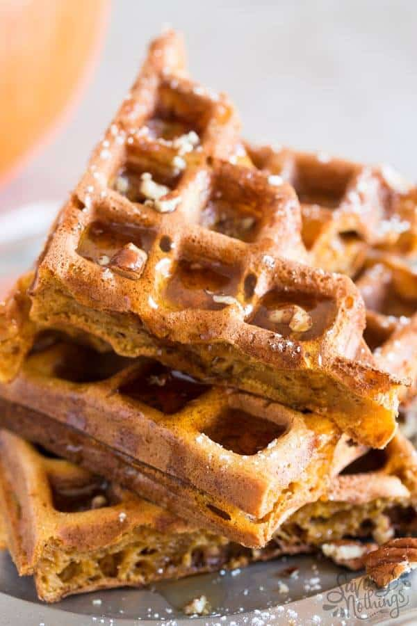 stack of pumpkin waffles sprinkled with pecans and drizzled with syrup
