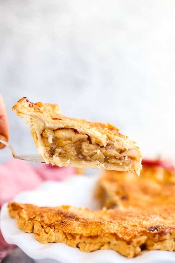 lifting a slice of apple pie out of the pie dish