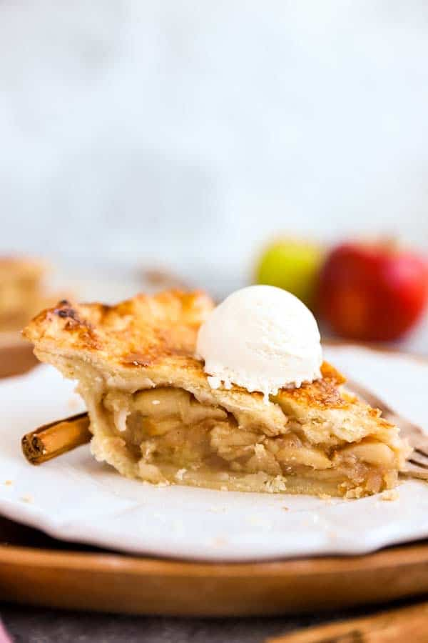 slice of apple pie on a plate, topped with a scoop of vanilla ice cream