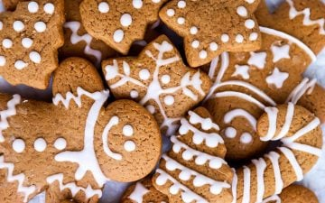 pile of gingerbread men and gingerbread cookie shapes decorated with icing
