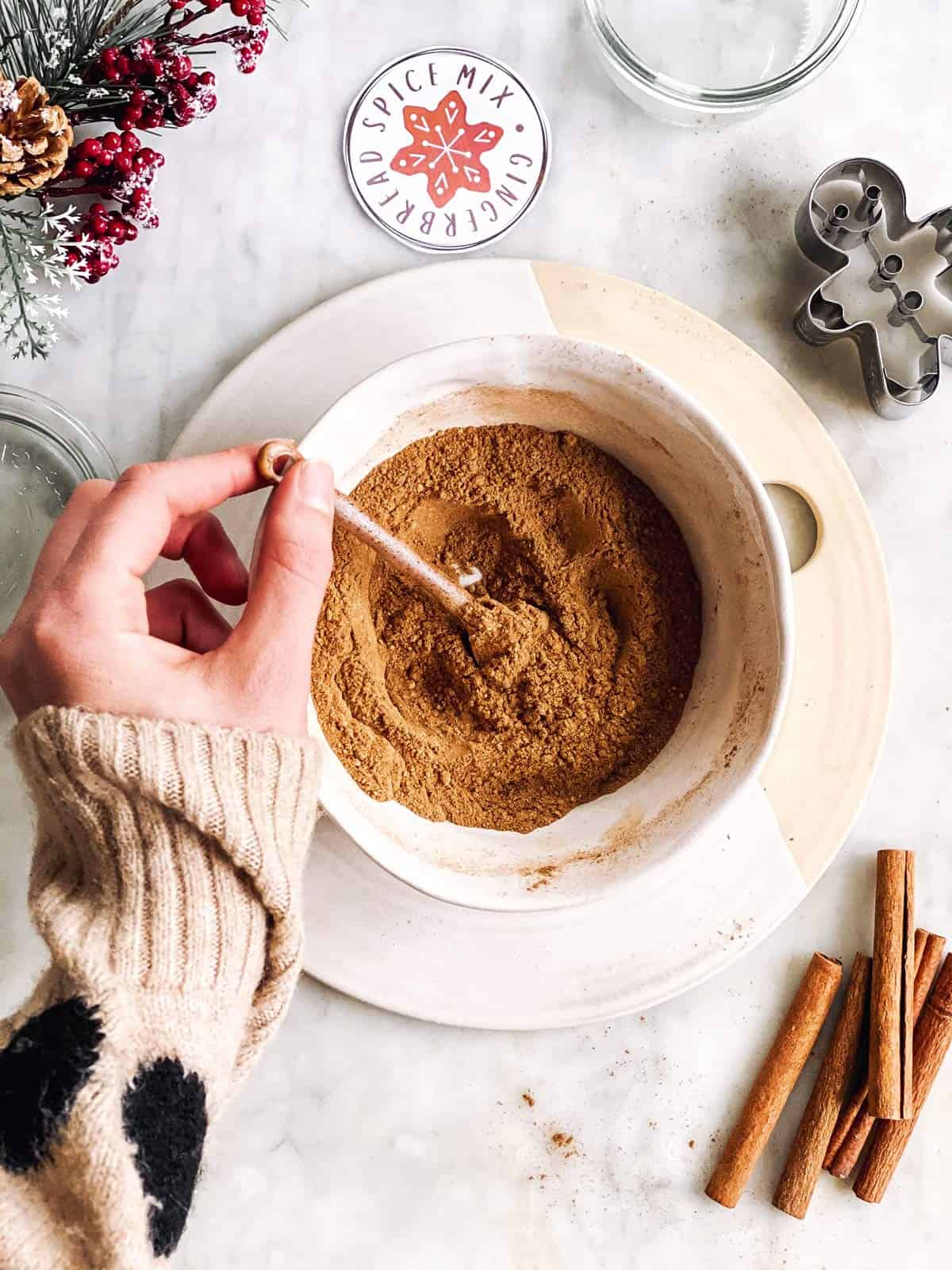 female hand stirring spices to make gingerbread spice mix in a white bowl