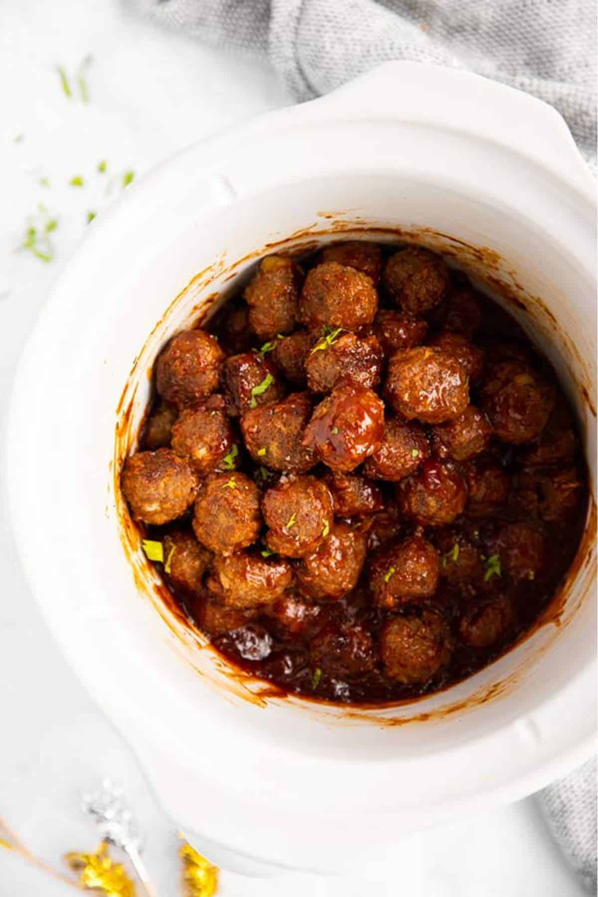 close up of white slow cooker with bbq meatballs