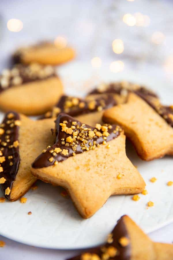 peanut butter shortbread cookie stars on a plate with chocolate glaze