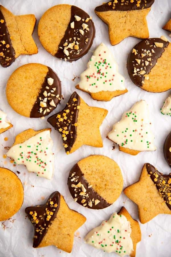 bunch of chocolate dipped shortbread cookies on a piece of baking parchment