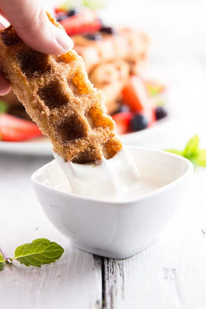 dipping a french toast waffle stick into cream cheese