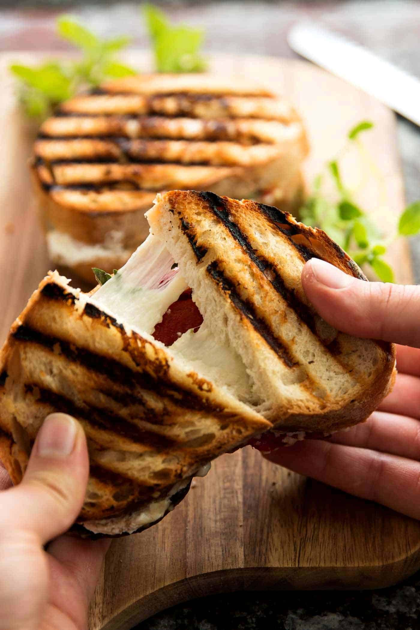 female hands pulling apart a grilled cheese sandwich