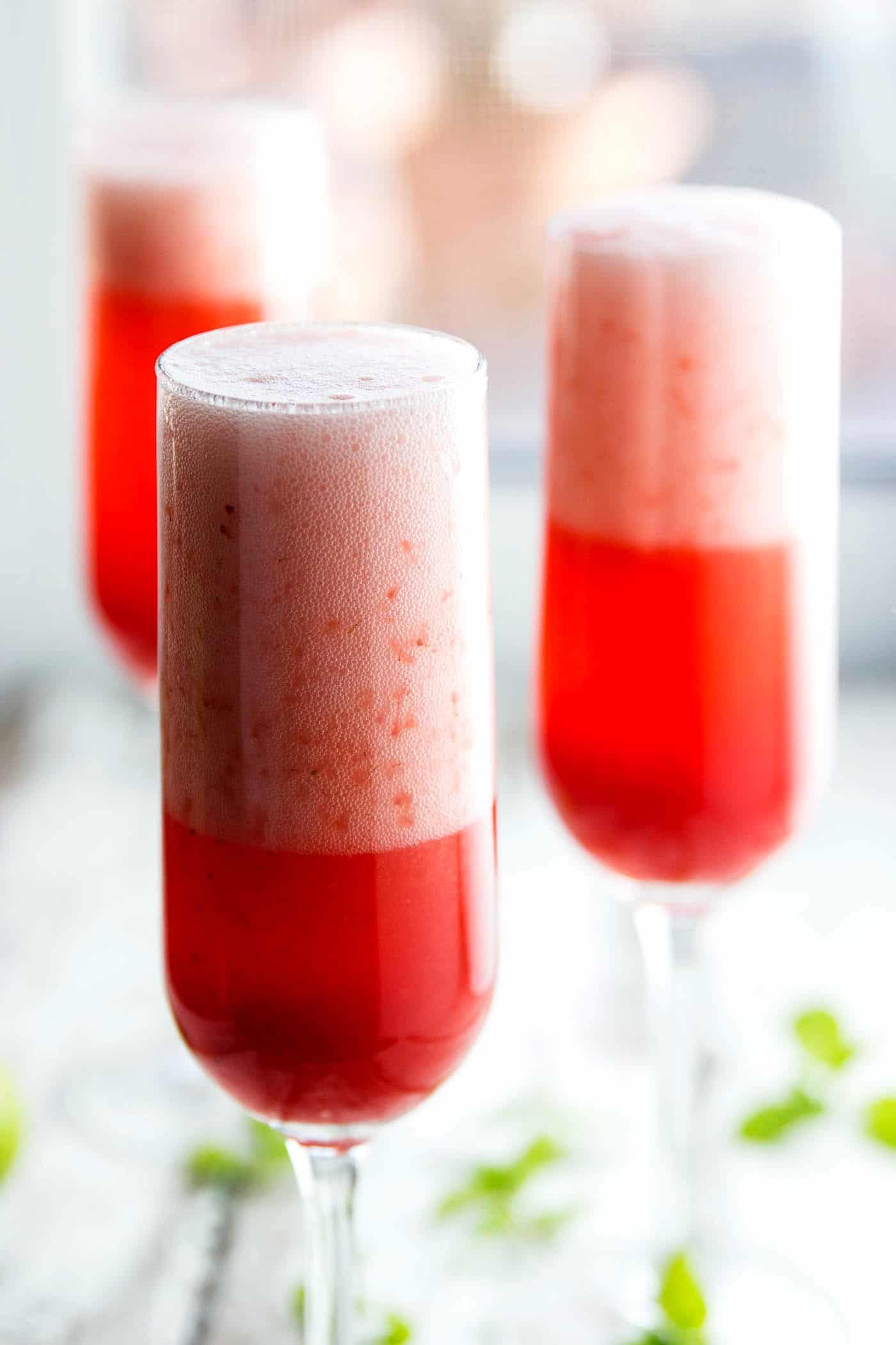 frontal view of three champagne glasses with strawberry champagne cocktail