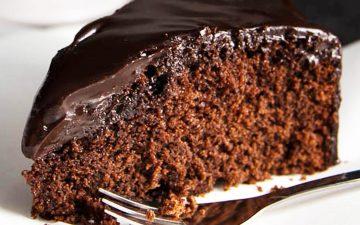 close up of chocolate honey cake on white plate