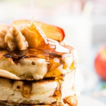 syrup drizzling over peach pancakes