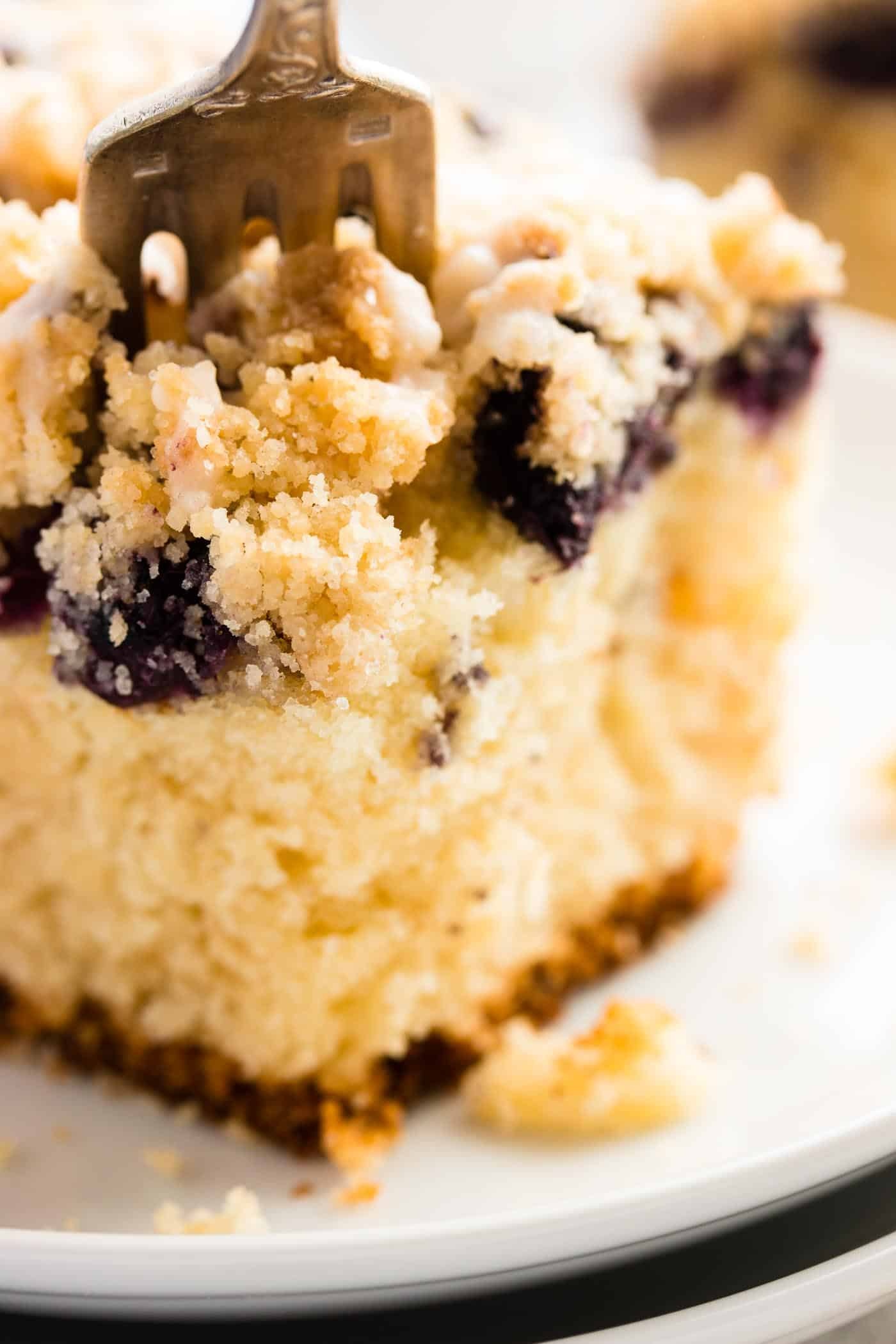 close up photo of fork stuck into a piece of lemon blueberry coffee cake