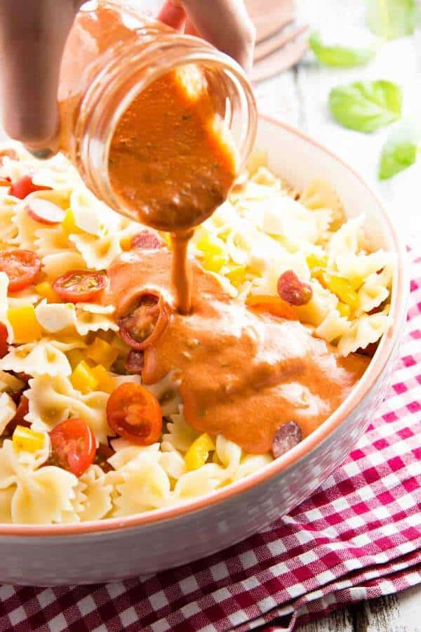 female hand pouring creamy dressing over pasta salad