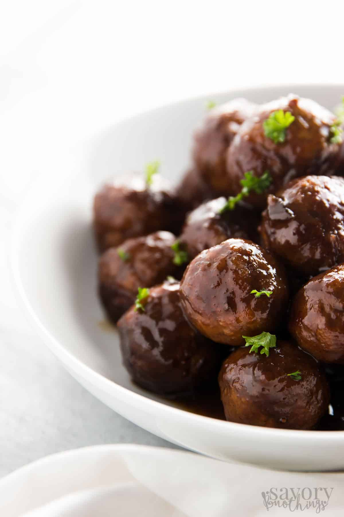 This easy Cranberry Glazed Turkey Slow Cooker Meatballs recipe is a real crowd pleaser at holiday parties and for football game day snacking. It uses 100% juice and honey for a healthier glaze. | savorynothings.com