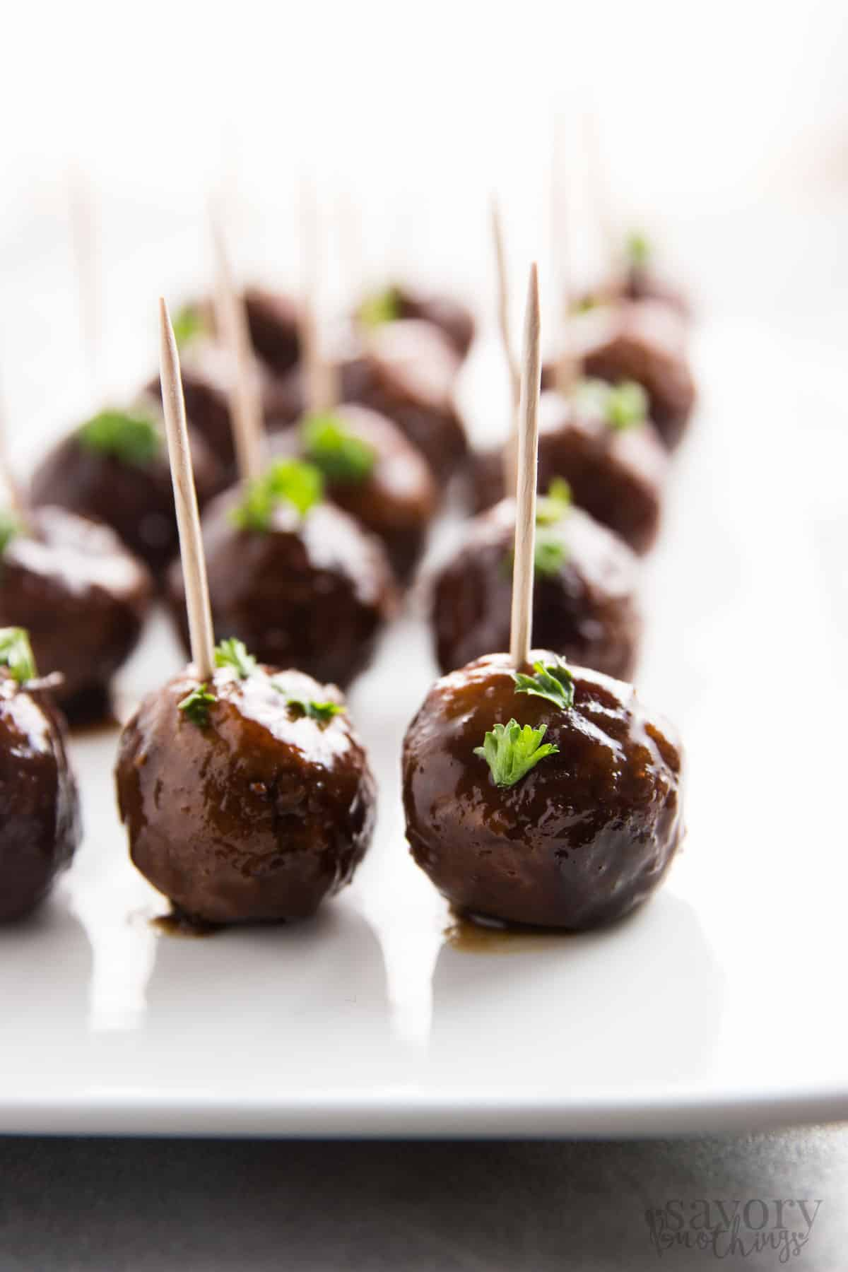 cranberry turkey meatballs on white platters with toothpicks