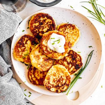 overhead view of potato pancakes on white plate with sour cream