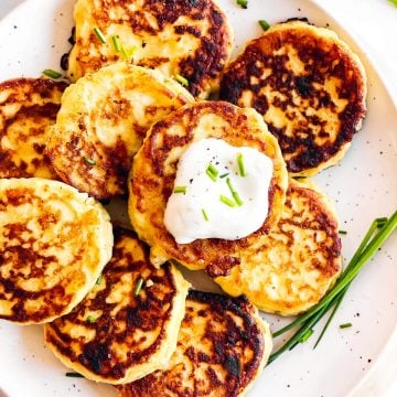 overhead close up view of potato pancakes on white plate with sour cream