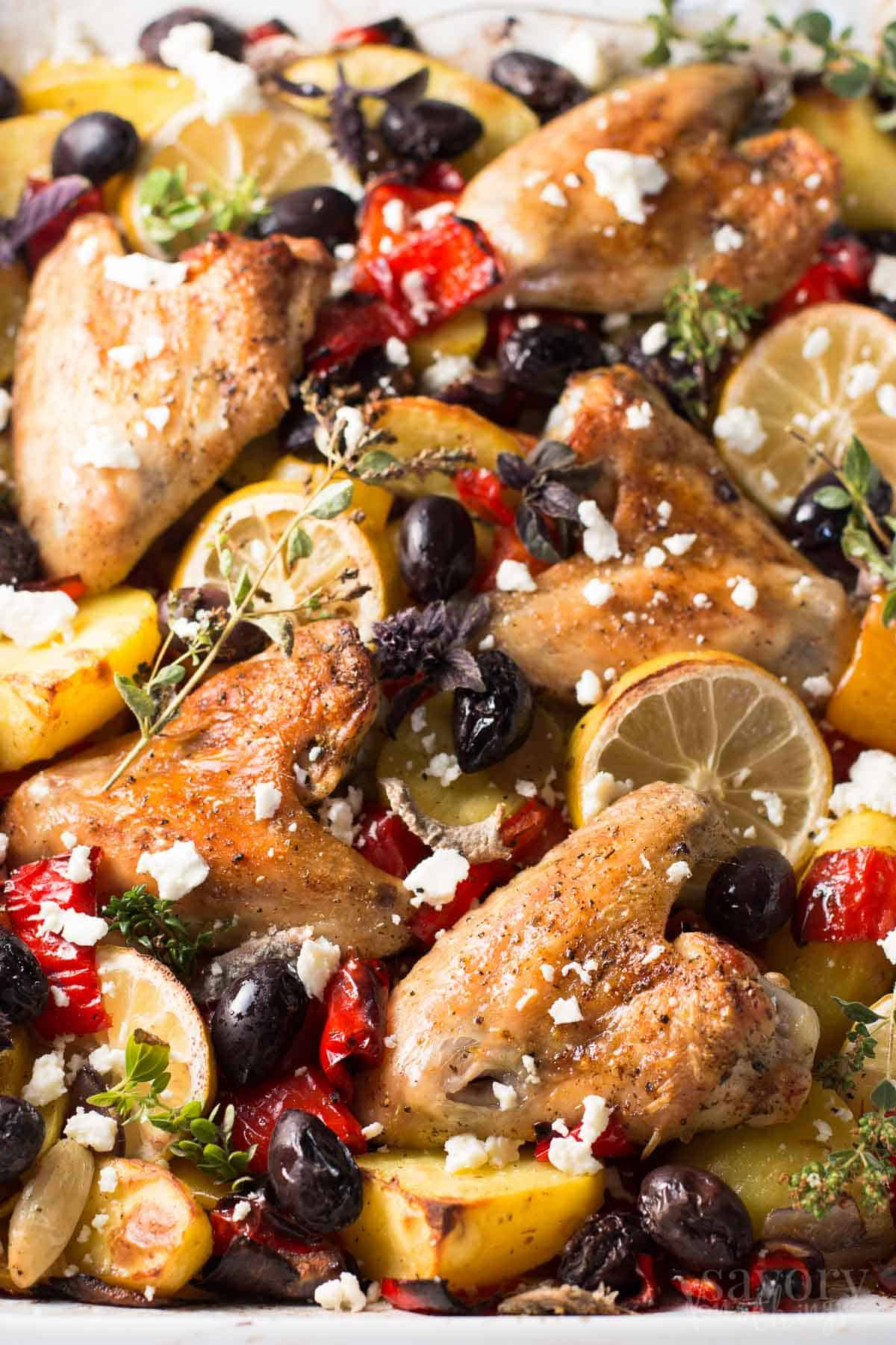close up photo of greek chicken casserole with lemon slices and olives