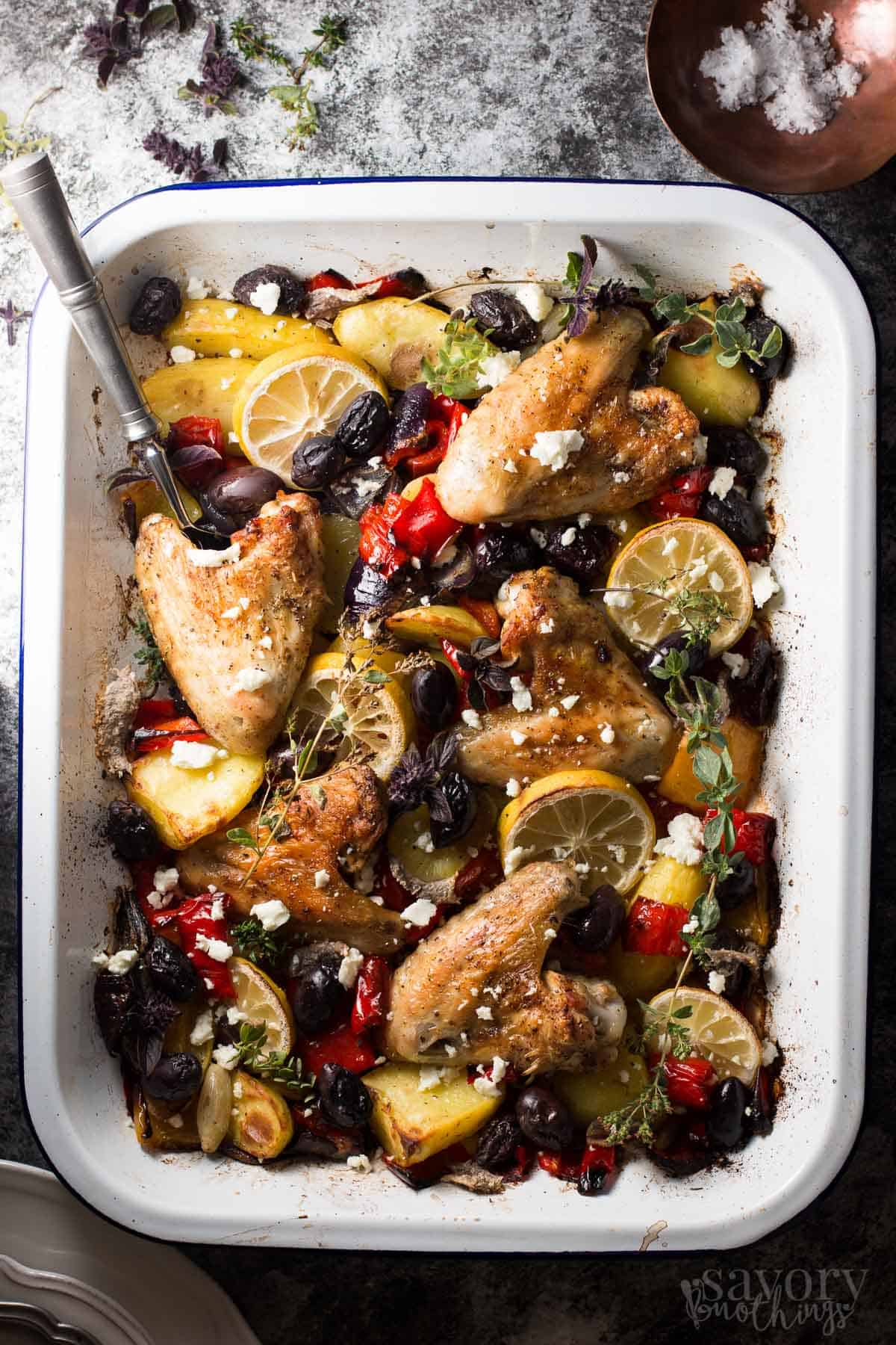 This One Sheet Pan Greek Style Easy Baked Chicken Dinner will save you at dinner time! You can throw everything onto your sheet pan and let it bake into a delicious dinner. The sauce that forms is so good! | savorynothings.com