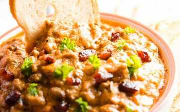 dipping a bread chip into a bowl with crock pot bbq bacon cheeseburger dip