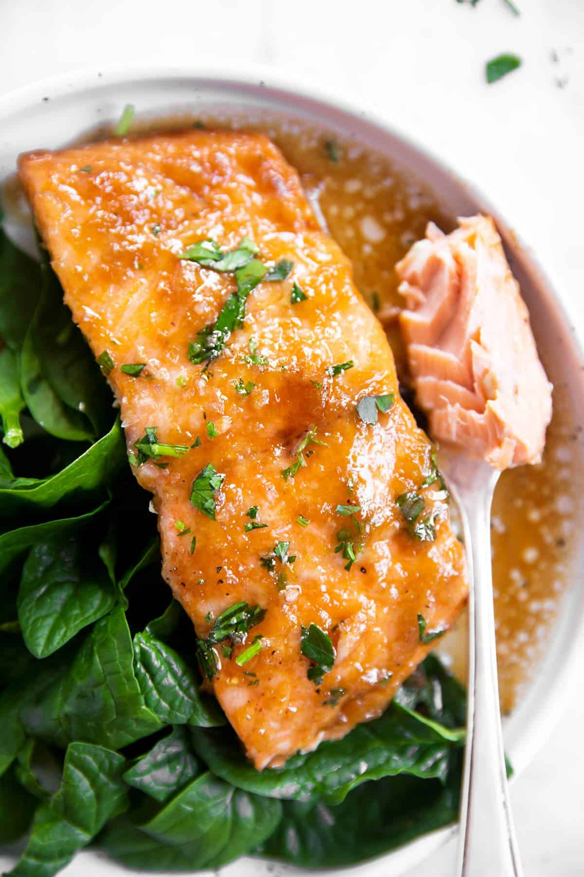 overhead view of honey garlic salmon bake in foil with spinach on plate