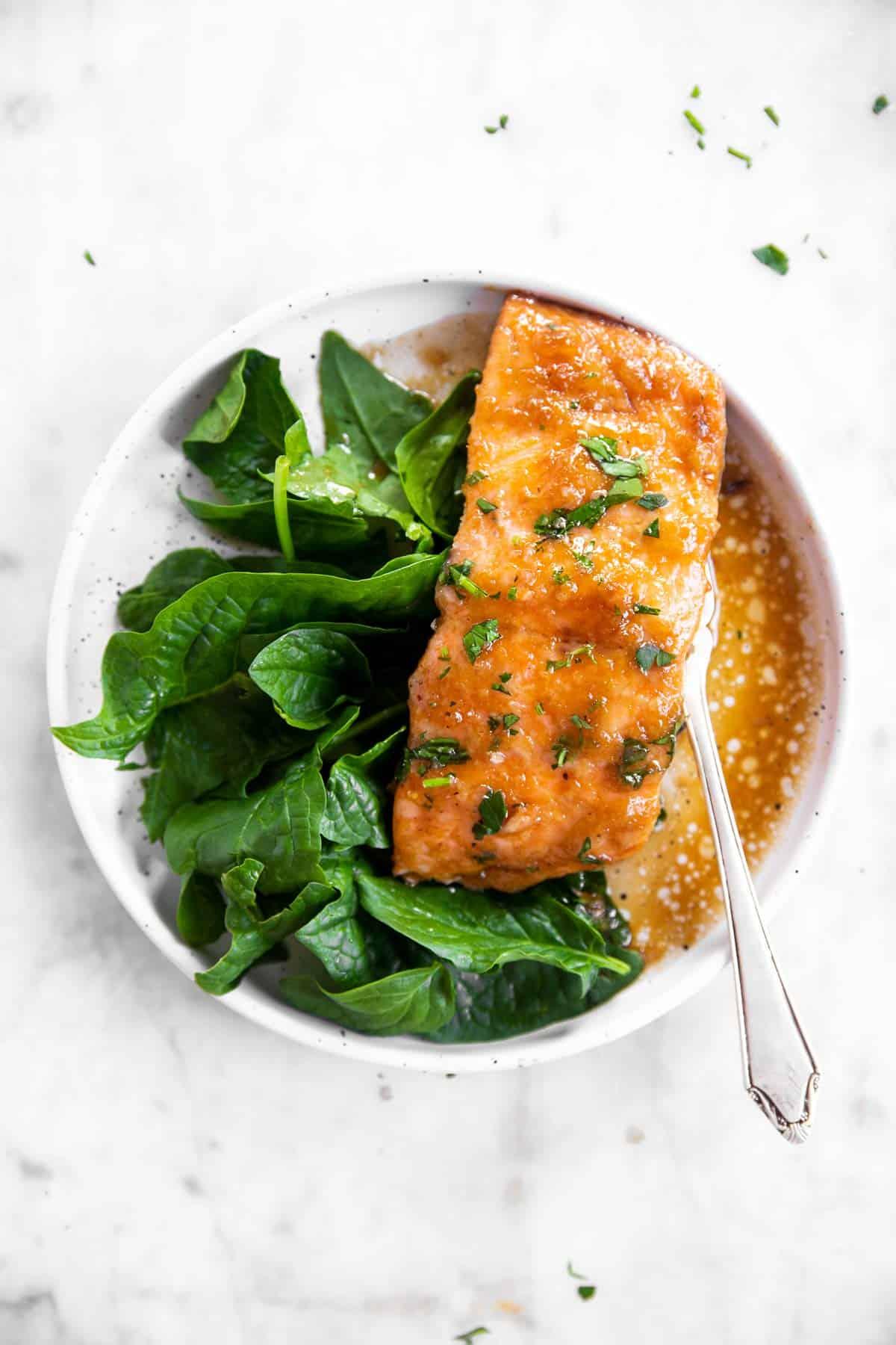 white plate with honey garlic baked salmon and spinach on white marble surface