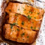 three salmon fillets in foil with honey garlic glaze