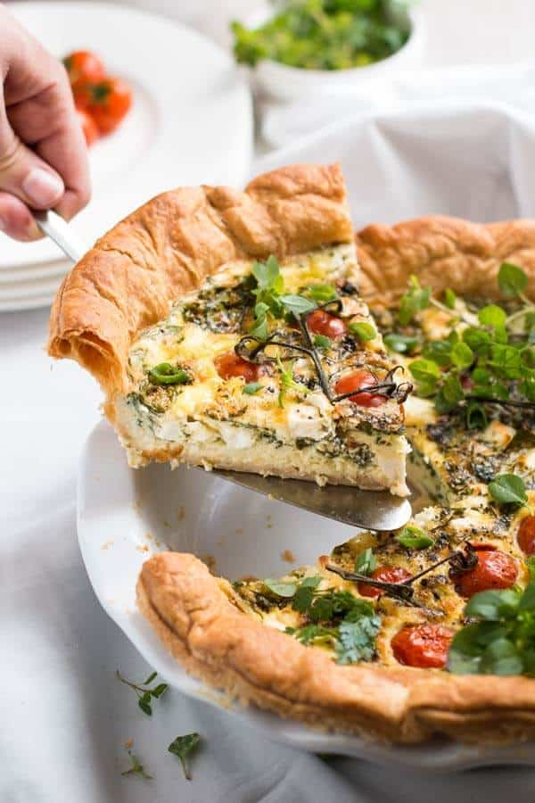 female hand holding cake scoop with a slice of feta quiche