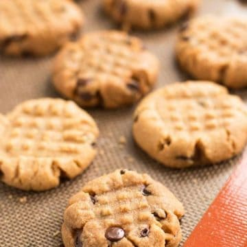 several chocolate chip peanut butter cookies on silicone baking mat