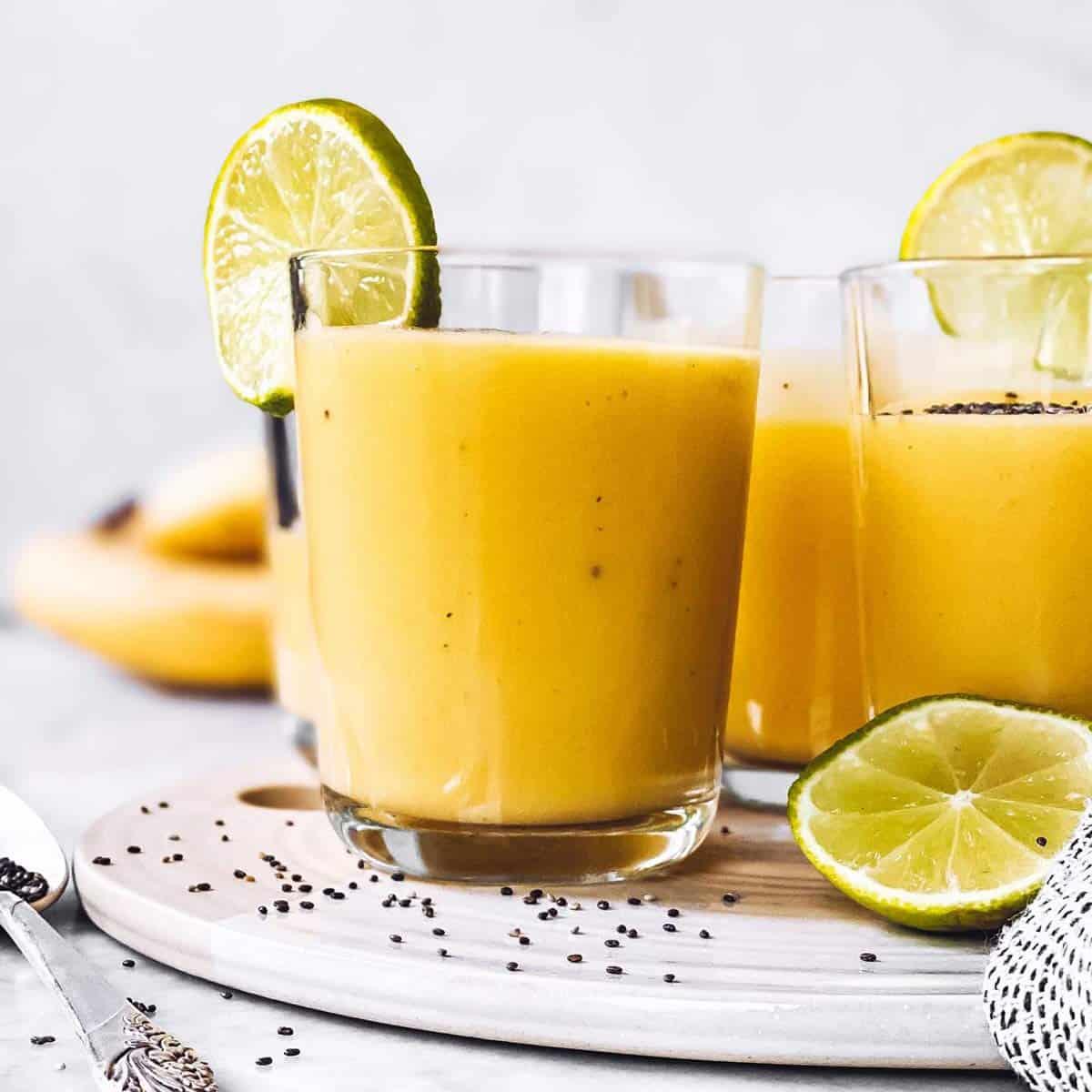 glasses with banana mango smoothie on platter
