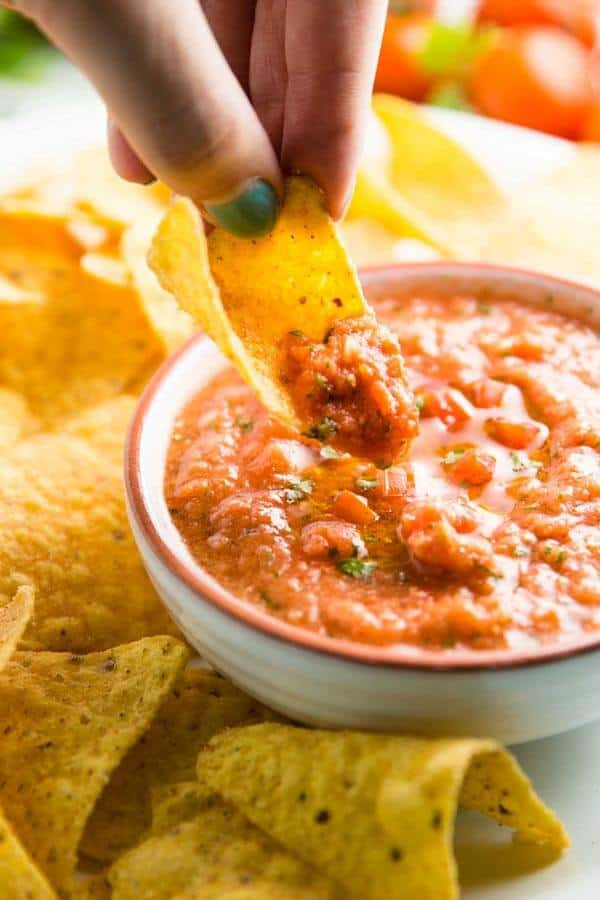 Dipping corn chips in blender salsa