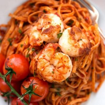 overhead closeup of shrimp on tomato pasta