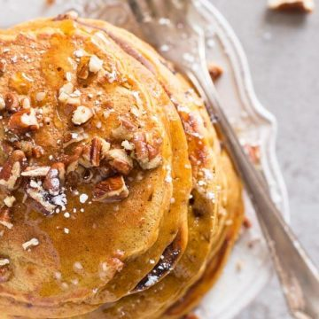 top down view on pumpkin pancakes and fork on white plate with chopped pecan nuts