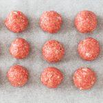 nine raw meatballs on parchment