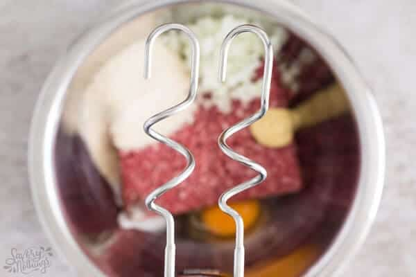 close up of hand mixer over bowl of meatball ingredients