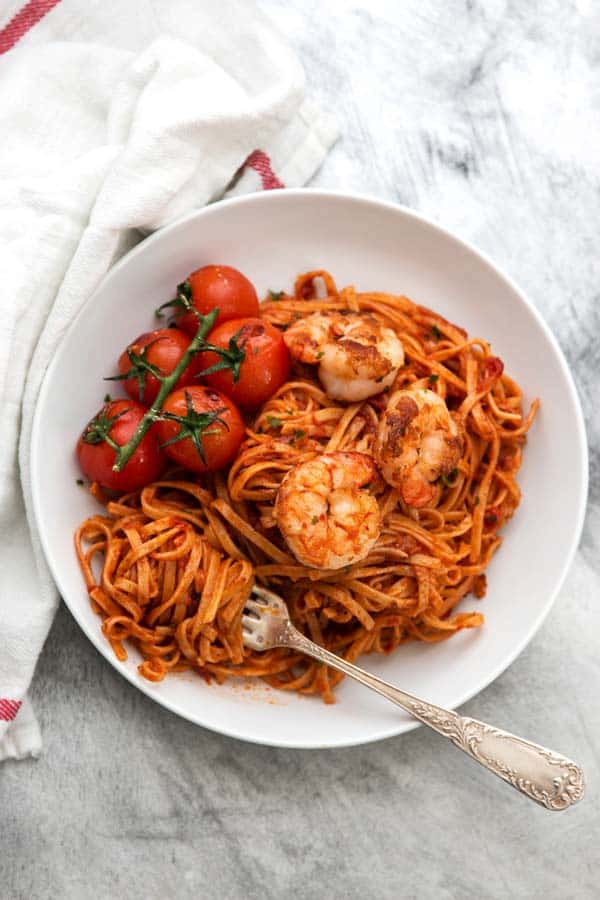 overhead photo of white plate with garlic butter tomato shrimp pasta