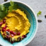 Turmeric Hummus in a blue bowl.