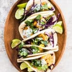 overhead view on wooden platter with five shrimp tacos and fresh lime slices