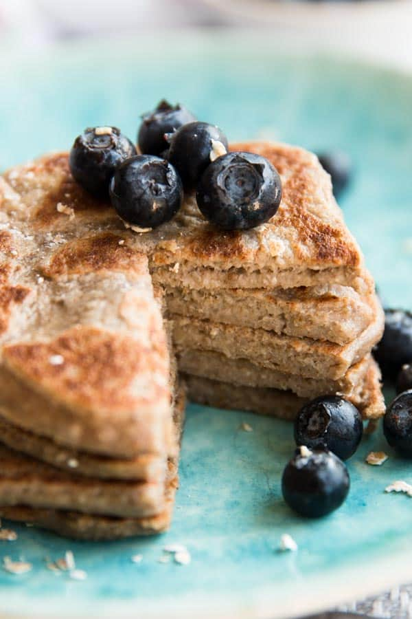 cut open stack of vegan banana pancakes on blue plate with fresh blueberries