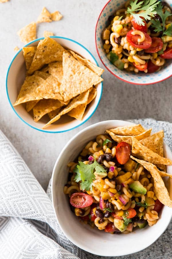 overhead view on bowls with Mexican macaroni salad and tortilla chips