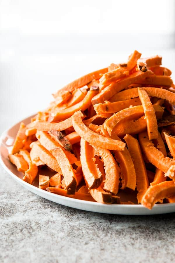 file of raw sweet potatoes cut into fries on white plate