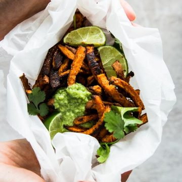 overhead view on female hands holding sweet potato fries wrapped in baking parchment