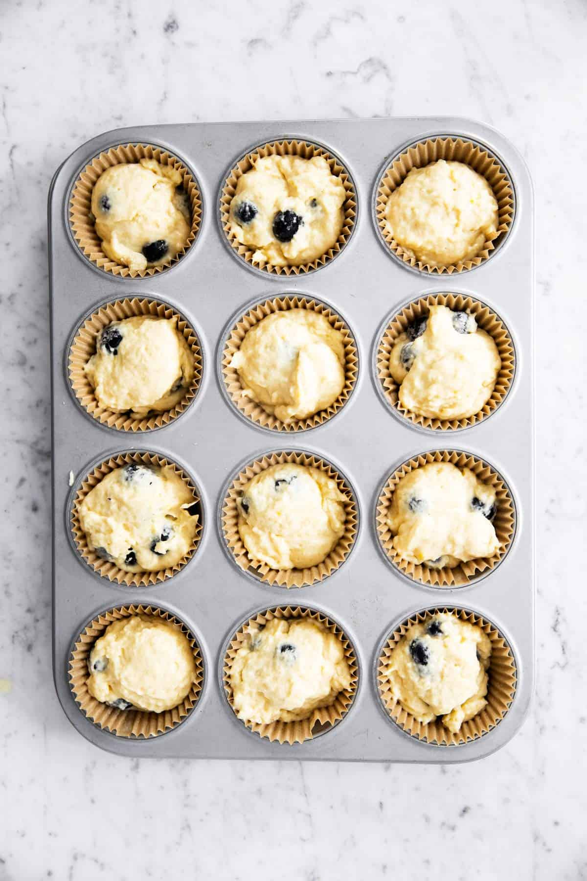 muffin cups filled with blueberry muffin batter