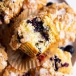 overhead view of blueberry muffin with bite taken out on plate with more muffins