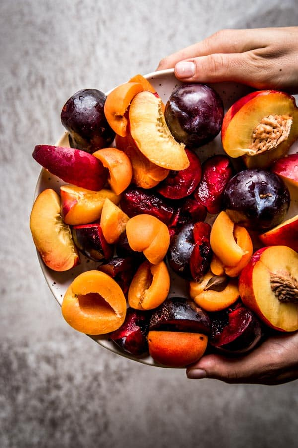 Sliced stone fruit held on a pottery plate. Beautiful food photography, still life.