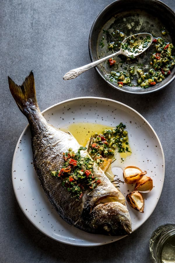 overhead view on baked whole baked fish on white plate with caper salsa