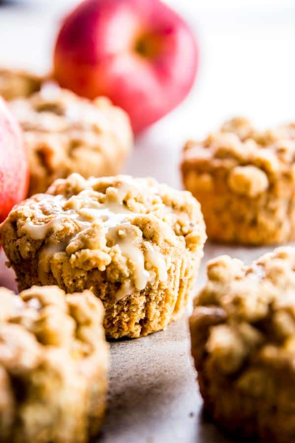 Apple cinnamon muffins made with greek yogurt on the counter with a fresh apple in the background.