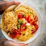 female hands holding plate with caprese pasta